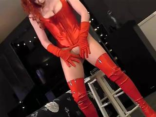 Redhead masturbates in a corset pantyhose and boots